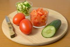 Interi cetrioli, pomodori ed insalata di loro su un tagliere Immagini Stock Libere da Diritti