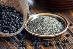 Interi e granelli di pepe neri a terra sulla vecchia tavola di legno Varietà del granello di pepe Pepe nero macinato Semi del pep Fotografia Stock
