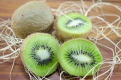 Interi e kiwi affettati su una tavola Fotografia Stock Libera da Diritti