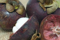 Interi frutti del mangostano delizioso maturo ed affettato sulla toppa della fine della borsa della canapa sulla foto fotografie stock