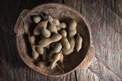 Interi frutti del tamarindo in ciotola di legno Fotografia Stock Libera da Diritti