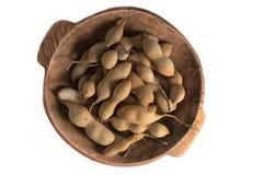 Interi frutti del tamarindo in ciotola di legno rotonda Immagini Stock Libere da Diritti