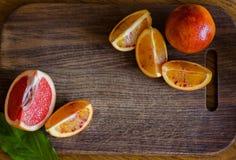 Interi frutti siciliani freschi dell'arancia sanguinella ed arancia e pompelmo affettati su fondo di legno Fotografia Stock Libera da Diritti