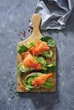 Interi panini del pane del grano con il cetriolo, le foglie degli spinaci, l'avocado ed il salmone affumicato freschi immagine stock libera da diritti