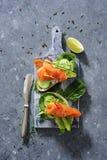 Interi panini del pane del grano con il cetriolo, le foglie degli spinaci, l'avocado ed il salmone affumicato freschi immagini stock