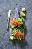 Interi panini del pane del grano con il cetriolo, le foglie degli spinaci, l'avocado ed il salmone affumicato freschi immagini stock libere da diritti