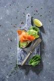 Interi panini del pane del grano con il cetriolo, le foglie degli spinaci, l'avocado ed il salmone affumicato freschi fotografia stock libera da diritti