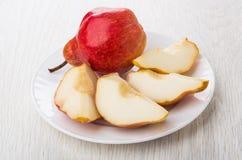 Interi pera e pezzi rossi di pera in piatto Fotografie Stock Libere da Diritti