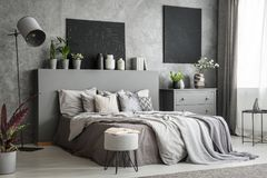 Interior à moda do quarto no cinza com uma cama grande com bedsheets, foto de stock