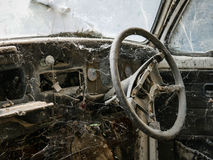 Interior of abandoned old car with spider web. Damaged dashboard, creepy and  gloomy atmosphere, scary background Stock Image