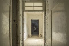 Interior of abandoned sanatorium in Portugal. Old corridor, doors frame, scary ambient royalty free stock image