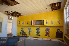 Interior of Abandoned School Room. Yellow wall with paintings of cartoons inside an old abandoned school room in Marshall Oklahoma. Ceiling titles are falling stock images