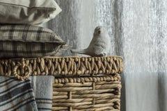 Interior acogedor con la cesta de mimbre y la tela escocesa y el pájaro de lana de la piedra Fotografía de archivo libre de regalías
