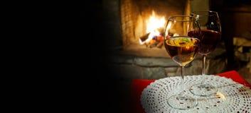 Interior acogedor de una tarde de Navidad Dos vidrios de vino blanco rojo, fondo de la chimenea de la chimenea postal romántica d fotografía de archivo