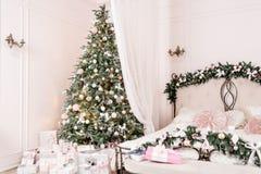 Interior acogedor del hogar de la Navidad Decoración del Año Nuevo sitio brillante del dormitorio con la cama matrimonial grande Imagen de archivo