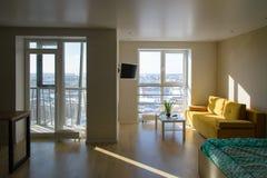 Interior acogedor moderno compacto del apartamento, sala de estar con el sofá amarillo, mesa de centro blanca y TV en la pared, v Foto de archivo libre de regalías