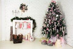 Interior agradable de la Navidad con un árbol, una chimenea y regalos de abeto Imagenes de archivo