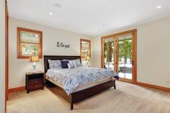 Interior agradable del cuarto de invitados con las puertas de cristal para apoyar el patio foto de archivo libre de regalías