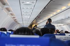 Interior of an airplane filled with passengers; air hostesses engaged in conversation,  before the safety demonstration
