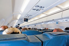 Interior of airplane with passengers on seats during flight Royalty Free Stock Image
