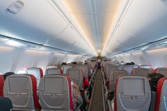 Interior of airplane with passengers on seats and stewardess in royalty free stock image