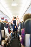 Interior of airplane with passengers on seats. Interior of airplane with passengers on seats and stewardess walking the aisle Royalty Free Stock Photo