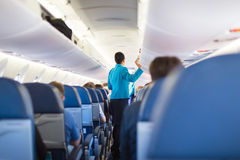 Interior of airplane with passengers on seats. Interior of airplane with passengers on seats and stewardess walking the aisle, closing the overhead luggage bins Royalty Free Stock Photography