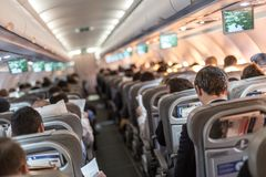 Interior of airplane with passengers on seats waiting to taik off. Interior of commercial airplane with passengers sitting and reading newspapers on seats Stock Photography