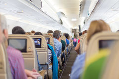 Interior of airplane with passengers on seats waiting to taik off. Interior of modern commercial airplane with passengers on their seats waiting to taik off Stock Photo