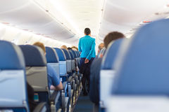 Interior of airplane with stewardess walking the aisle. Stock Photo
