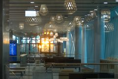 Interior of the airport hall in the evening, through panoramic glass the rays of the sun pass Royalty Free Stock Photography