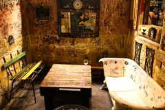Interior of an alternative bar. On one side an old wooden bench and on the other side a converted bathtub which functions as a seat. a wooden pallet as a table stock image