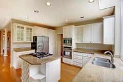 Interior americano clásico de la cocina con los gabinetes blancos y el refrigerador incorporado del acero inoxidable Fotos de archivo libres de regalías