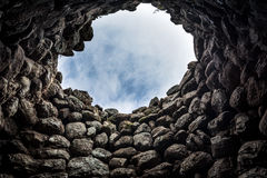 Interior of ancient ruins in Sardinia, Italy. Very old nuraghe interior with overhead opening to allow light in it. Nuraghic sites are archaeological remnants Royalty Free Stock Image