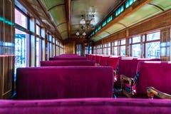 Interior antiguo del vehículo de pasajeros con los asientos rojos de la lumbrera foto de archivo