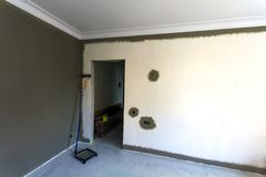 Interior of a apartement room during renovation work. Painting o. F the walls with dark paint Royalty Free Stock Images