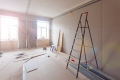 Interior of apartment during construction, remodeling, renovation, extension, restoration and reconstruction - ladde. R and construction materials in the room royalty free stock images