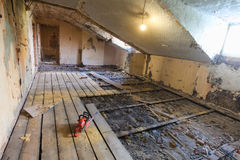 Interior of apartment  during on the renovation and construction. Chainsaw on partially dismantled wooden floor and sawdust. Interior of apartment during on the Stock Photo