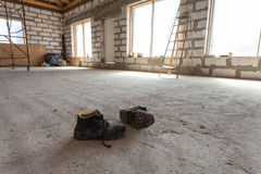 Interior of apartment  during under renovation, remodeling and construction a pair of working shoes on the cement floor Stock Photos