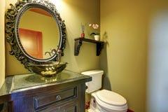 Interior asombroso del cuarto de baño con el fregadero de cristal del diseño y pote de la orquídea en el estante Foto de archivo libre de regalías