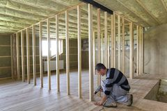 Interior of attic insulated room with oak floor under reconstruction. Young professional worker uses level and screwdriver. Installing wooden frame for future royalty free stock image