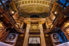 Interior of Austrian National Library. Vienna, Austria - December 24, 2017. Interior of Austrian National Library with craved wood bookshelves and molding royalty free stock image