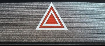 Interior automobile red and white hazard symbol. Interior sports car show a sexy gray metallic background dash with a red and white hazard symbol. black silver Stock Image