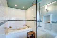 Interior azul do banheiro com a parede branca da guarnição da telha, o chuveiro de vidro da cabine e a banheira Imagem de Stock