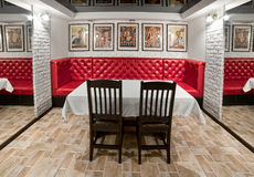 Interior banquet room with a large red sofa, table, chairs, mirr. Ors and paintings Stock Image