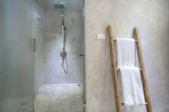 Interior of bathroom with modern shower head and white towel at rail in bathroom stock image