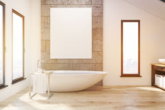 Interior of a bathroom with narrow windows, wooden tub, concrete and white walls Stock Photo