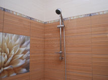 The interior of the bathroom orange and beige striped tiles, decoration with a lotus flower Royalty Free Stock Photo
