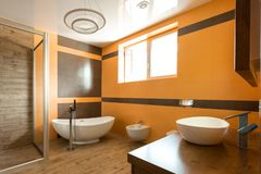 Interior of bathroom in orange and white colors with bathtube sink. And bidet stock photo