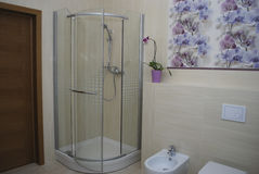 Interior bathroom shower with one door, built-in toilet and bidet. Stock Photos